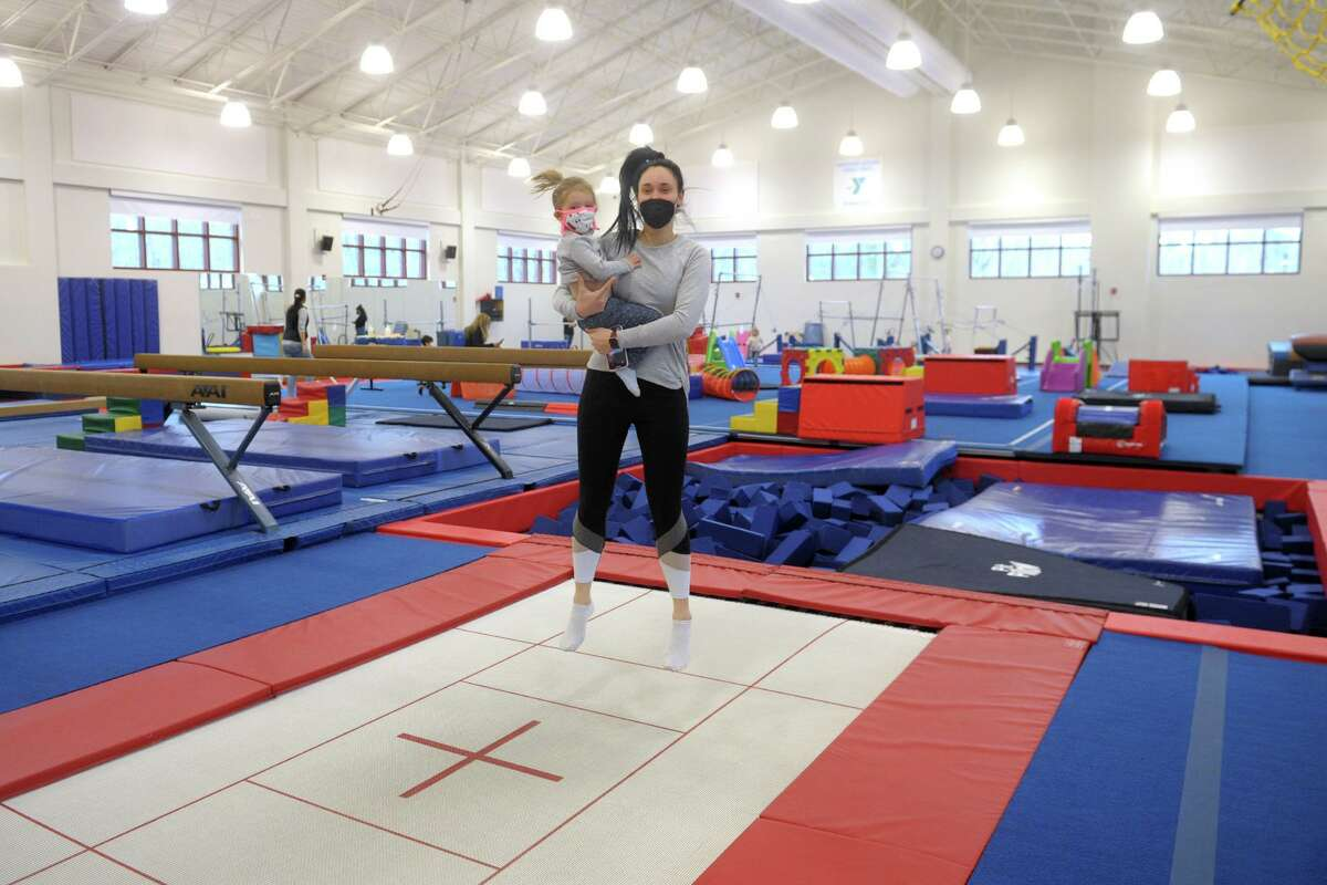 Eliza Carey bounces on a trampoline in the arms of her au pair, Bernelee Kritzinger, during a visit to a gymnasium of the Westport Weston Family YMCA, in Westport, Conn. March 16, 2021.