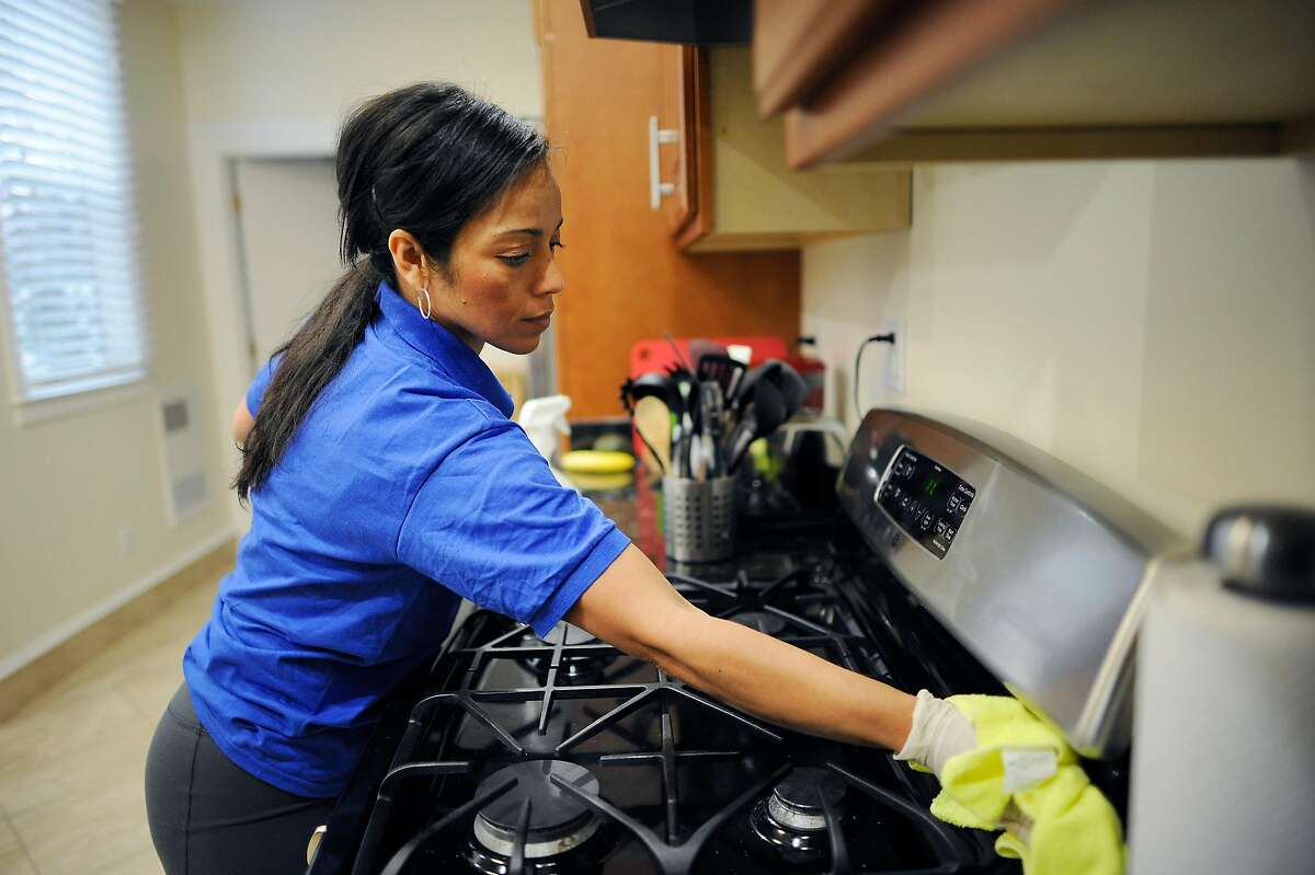 District attorneys in San Francisco and Los Angeles contend that workers like Katia Nuñez, a maid shown cleaning a San Francisco home in 2014, are misclassified by Handy.com as contractors.