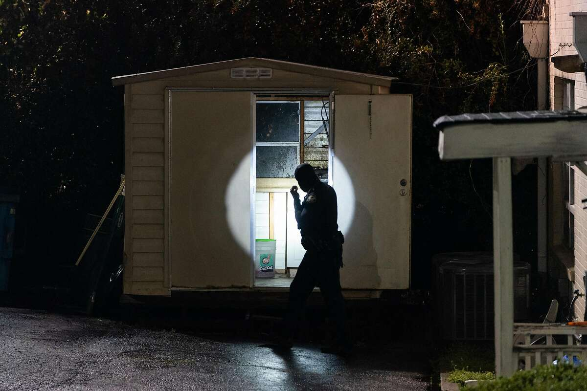 A police officer uses a flashlight to look in a shed outside a massage parlor where three people were shot and killed on March 16, 2021, in Atlanta, Georgia. Eight people were killed in shootings at three different spas in the US state of Georgia on March 16, police and local media reported. The suspect, named as 21-year-old Robert Aaron Long, is in police custody. (Elijah Nouvelage/AFP/Getty Images/TNS)