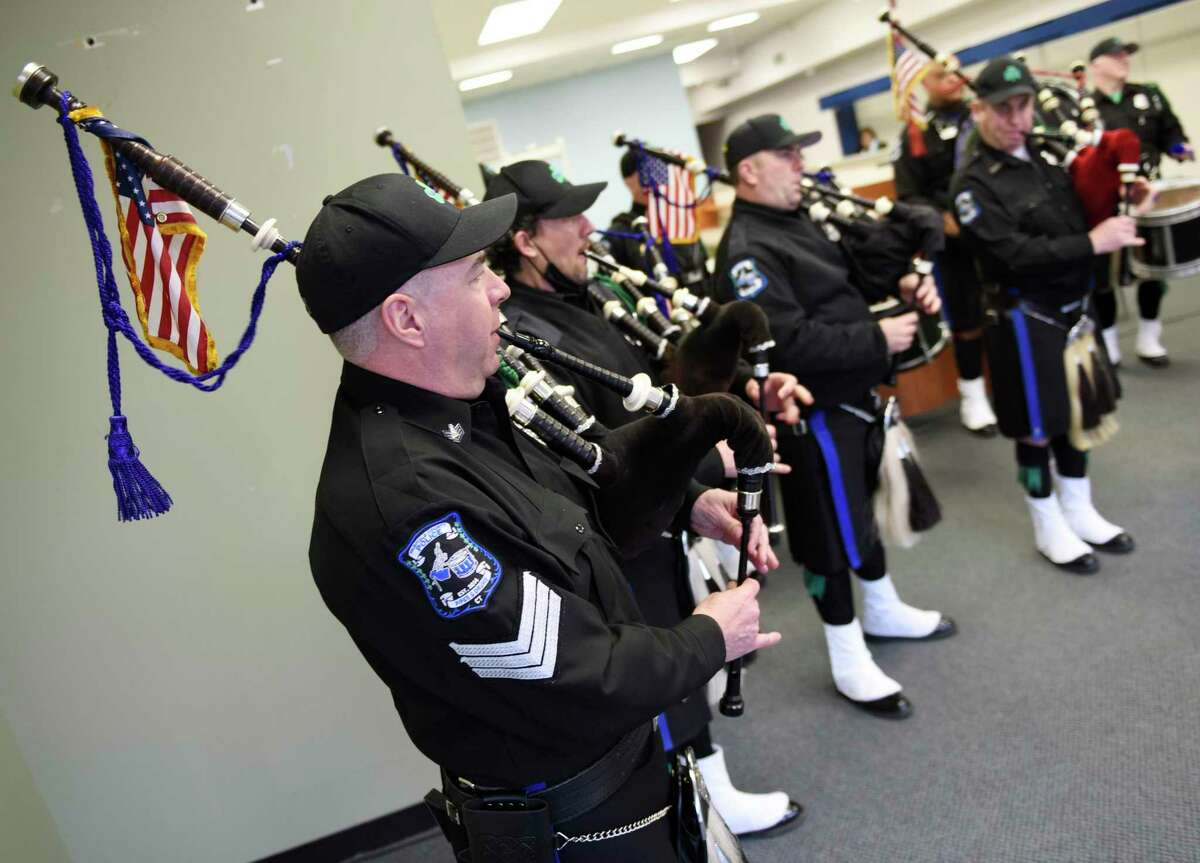 Fairfield County Police Pipes and Drums perform a concert in Stamford on Wednesday in celebration of St. Patrick's Day for passersby in the window of a vacant store on Bedford Street. The group, which is comprised of former and current police officers through Fairfield County, plans to hold more pop-up window performances throughout the year.