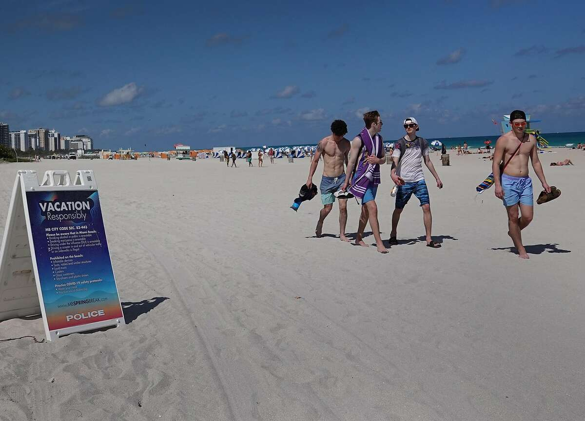 MIAMI BEACH, FLORIDA - MARCH 16: People walk past a sign advising everyone to vacation responsibly as enjoy themselves on the beach on March 16, 2021 in Miami Beach, Florida. College students have arrived in the South Florida area for the annual spring break ritual. City officials are concerned with large spring break crowds as the coronavirus pandemic continues. They are advising people to wear masks if they cannot social distance. (Photo by Joe Raedle/Getty Images)
