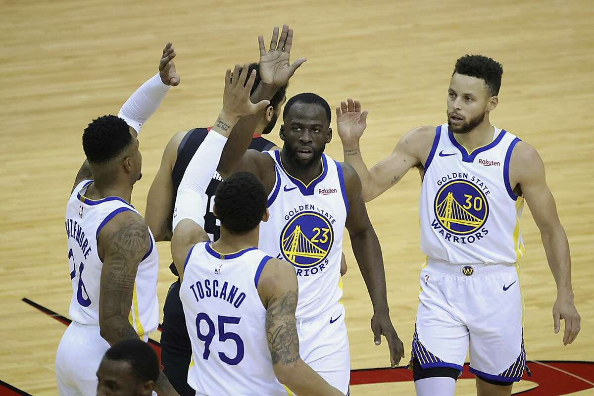 Golden State Warriors' Draymond Green (23) high-fives Kent Bazemore, left, Stephen Curry (30) and Juan Toscano-Anderson (95) during the first quarter against the Houston Rockets in an NBA basketball game Wednesday, March 17, 2021, in Houston. (Carmen Mandato/Pool Photo via AP)
