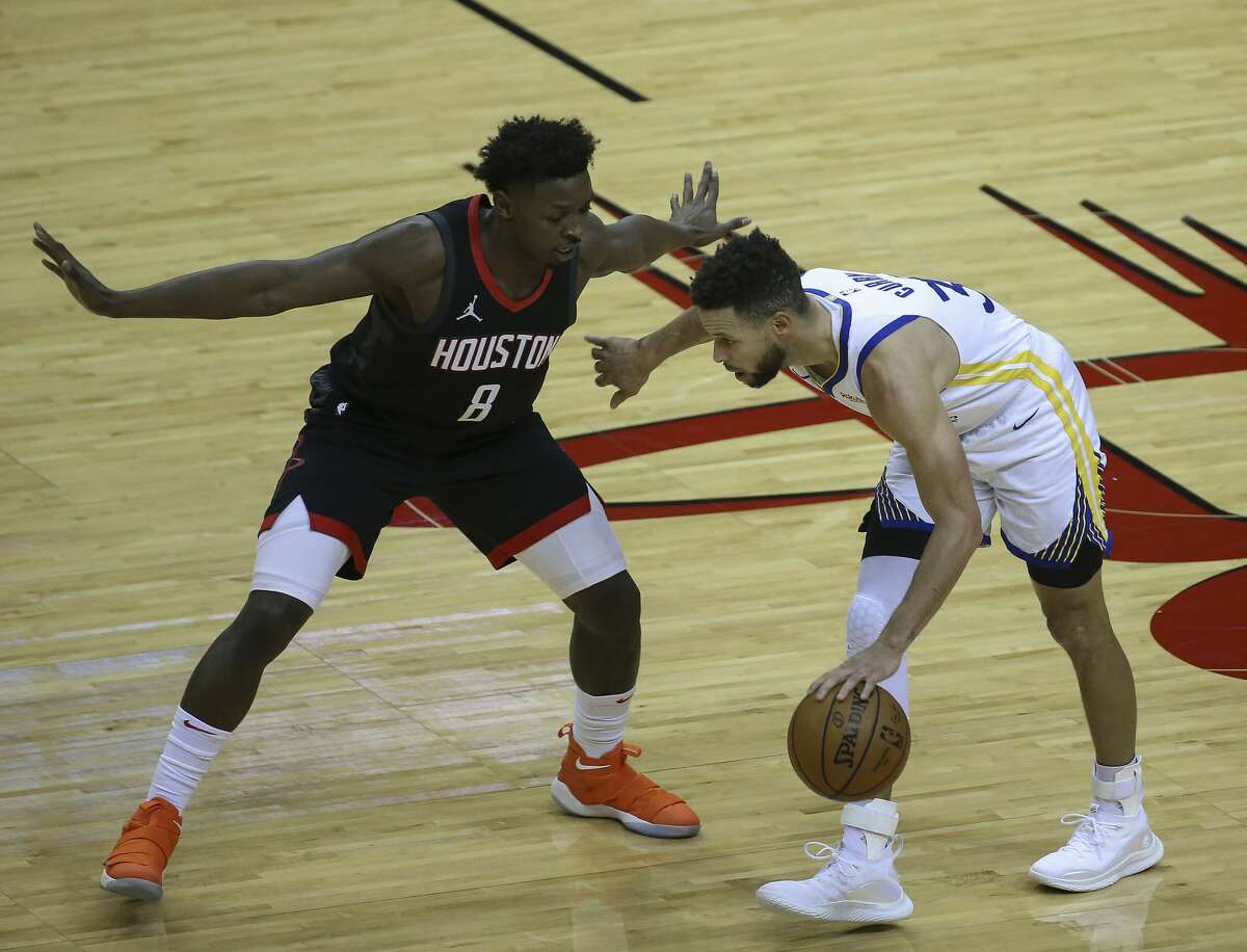 Houston Rockets forward Jae'Sean Tate (8) defensing Golden State Warriors guard Stephen Curry (30) during the first quarter of the NBA game Wednesday, March 17, 2021, at Toyota Center in Houston.