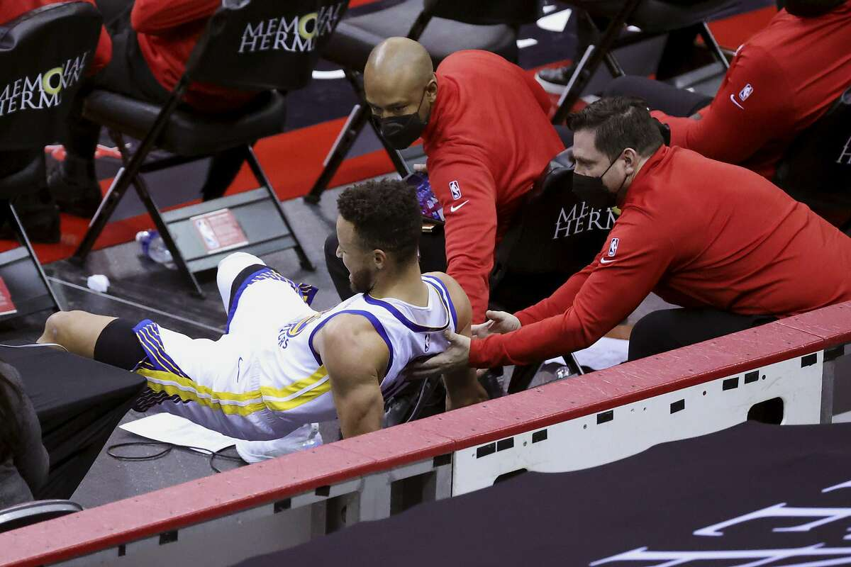 Stephen Curry is helped by staff members after falling into the Rockets' bench in Houston on March 17. The Warriors' guard missed six of the next eight games because of the injury.