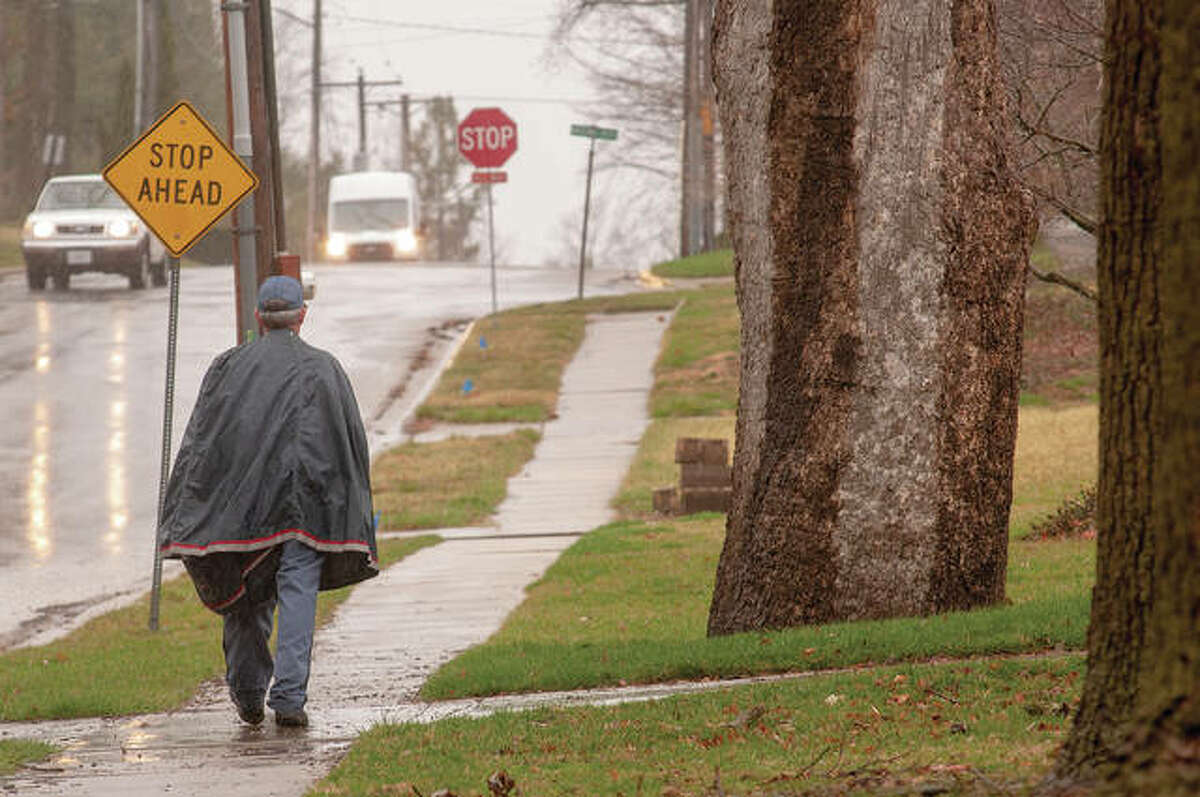 U.S. Postal Service worker David Helmich delivers mail Wednesday, despite rain and winds that were gusting to about 30 mph. Helmich joked that he tried to get another person to deliver mail for him. The National Weather Service said west-central Illinois could see heavy rains today with some flooding possible.