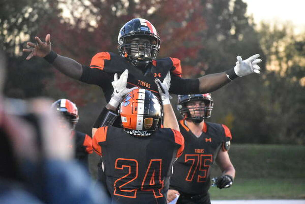 Edwardsville running back Justin Johnson Jr. is lifted into the air by teammate Jacob Morrissey after scoring a touchdown in the Class 8A postseason opener against St. Charles East.
