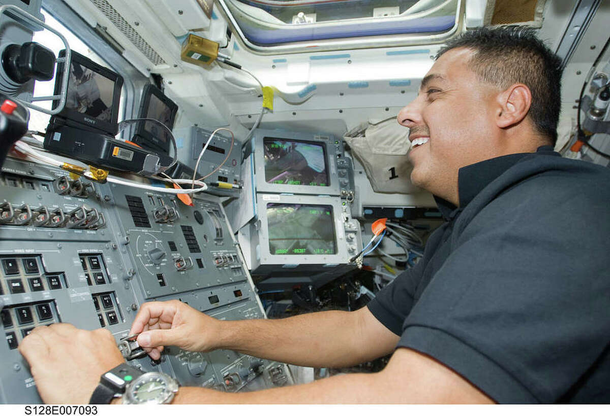 Former astronaut José Hernández working controls on the flight deck of space shuttle Discovery while docked with the International Space Station on Aug. 31, 2009.