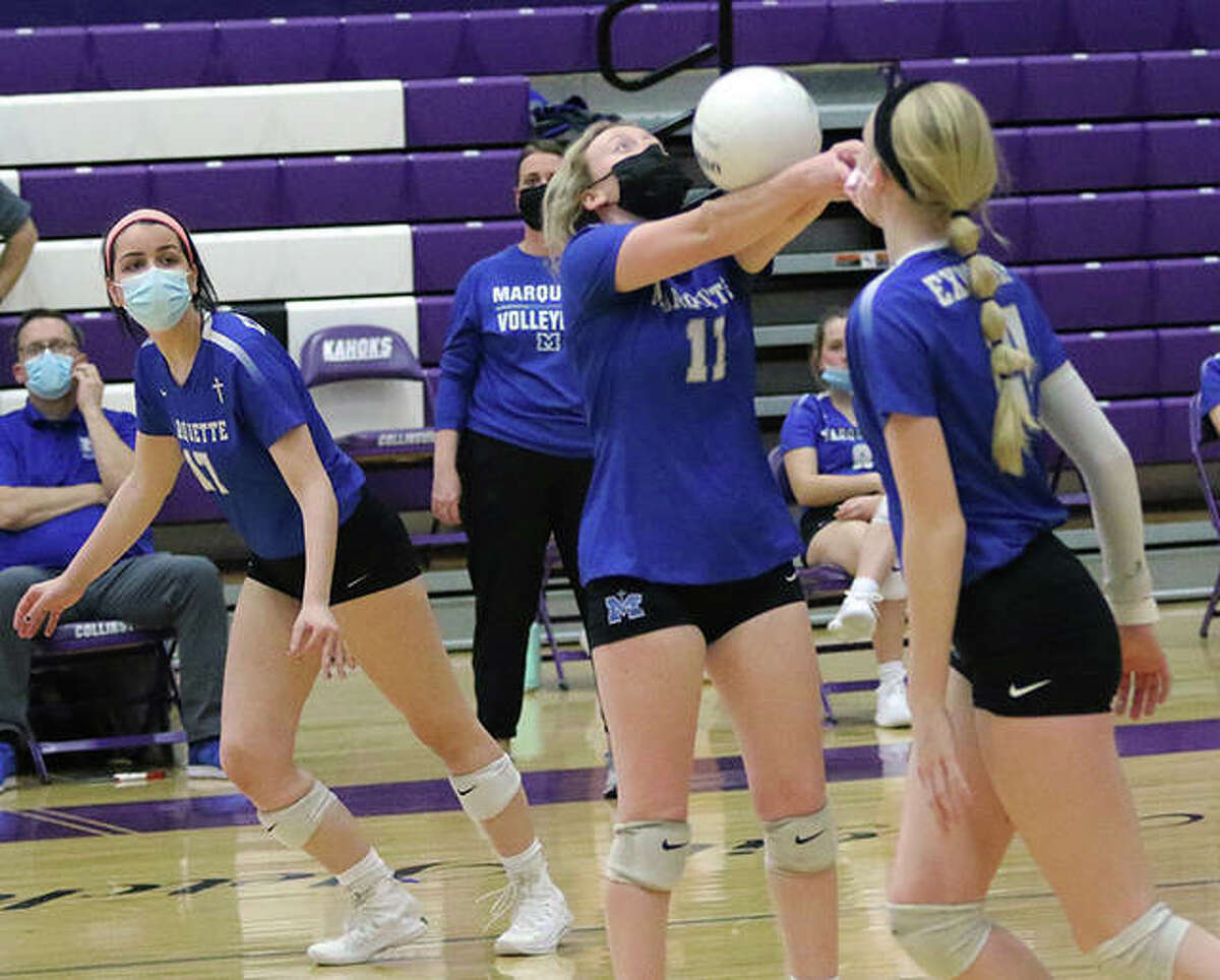 Marquette Catholic's Rachel Heinze (middle) bump sets while pin hitters Claire Spain (left) and Emma Menke head to the net in the first set of their two-set win Wednesday night over the host Kahoks at Fletcher Gym in Collinsville.