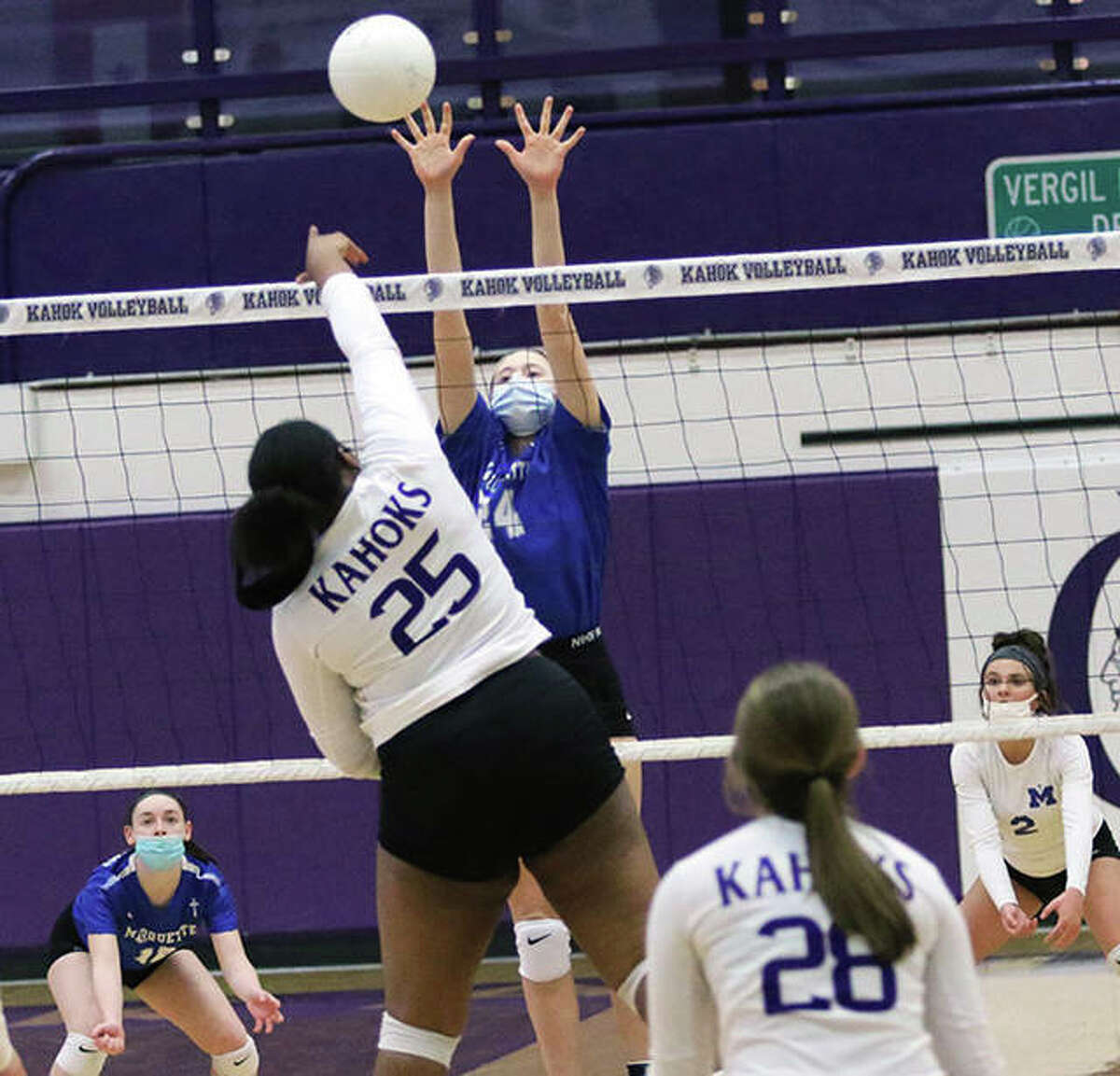 Collinsville's Kennedy Fisher (25) hits over the block of Marquette Catholic's Kylie Murray on Wednesday at Fletcher Gym in Collinsville.