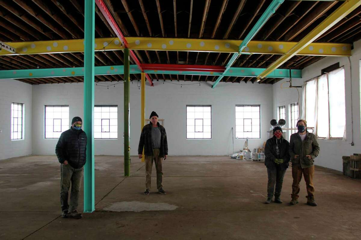 From left, Chris Boyle, Terry Boyle, Angela Napolitano, and Nick DeyArmond stand in the space that will become Pak's Garage. The four have been working on renovating a former scooter and bike factory into the new mixed-use space. (Robert Creenan/Huron Daily Tribune)
