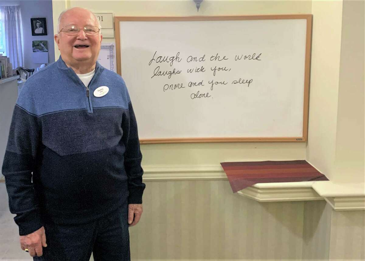 Henry Millan, a resident of Covenant Living of Cromwell, stands next to his white board where he writes a daily quote that provides inspiration for the difficulties many are facing during the pandemic.