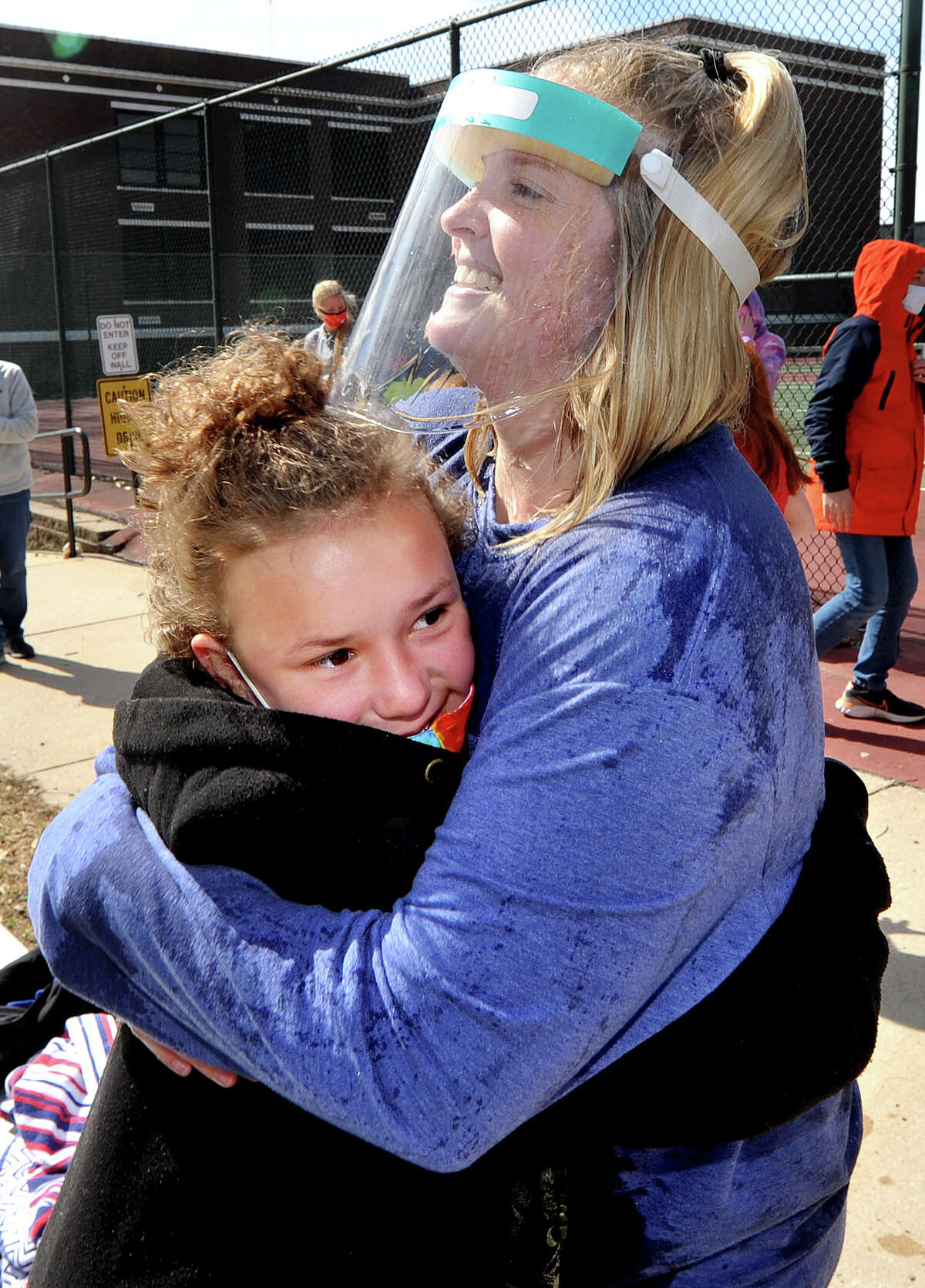 Lincoln Middle School Future Life Skills teacher Alyssa Smith (right) gets a hug from one of her students Aliana Robertson, 12, after Smith had cold water poured onto her during the Polar Plunge at the school Friday.