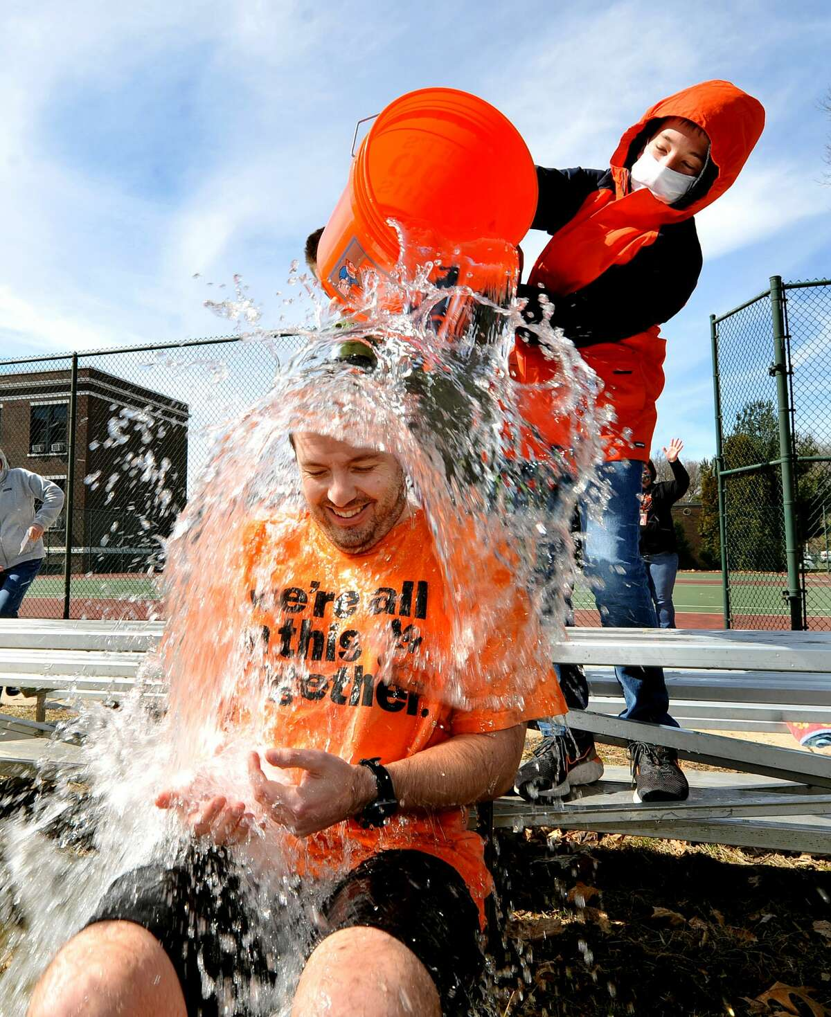 Assistant Super Intendent Adam Garrett, (left) gets cold water poured over his head by Spencer Schickedanz, 13, during the Polar Plunge at Lincoln Middle School Friday.