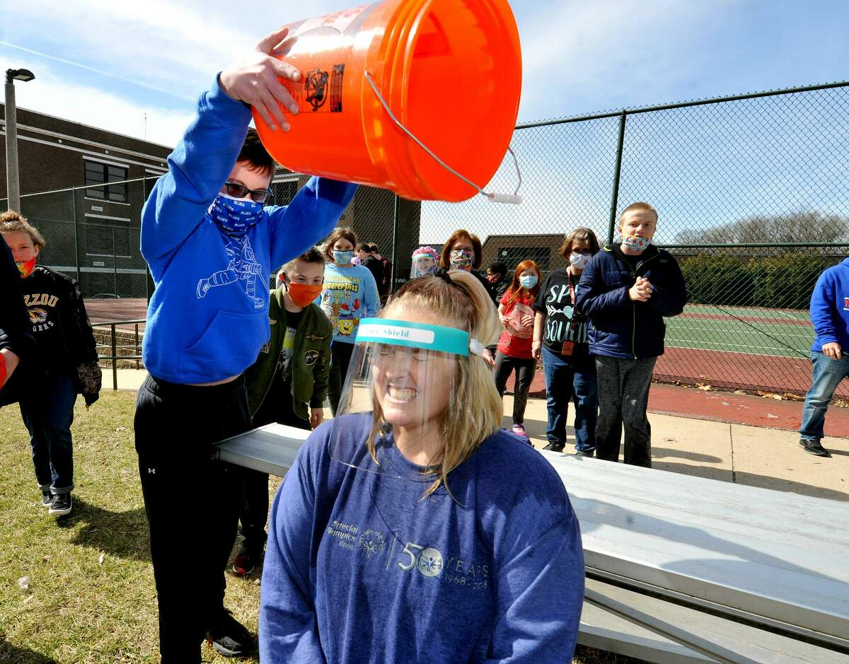 Lincoln Middle School student A.J. Brewster, 13, (left) pours a bucket of water onto Future Life Skills teacher Alyssa Smith during the Polar Plunge at the school Friday.