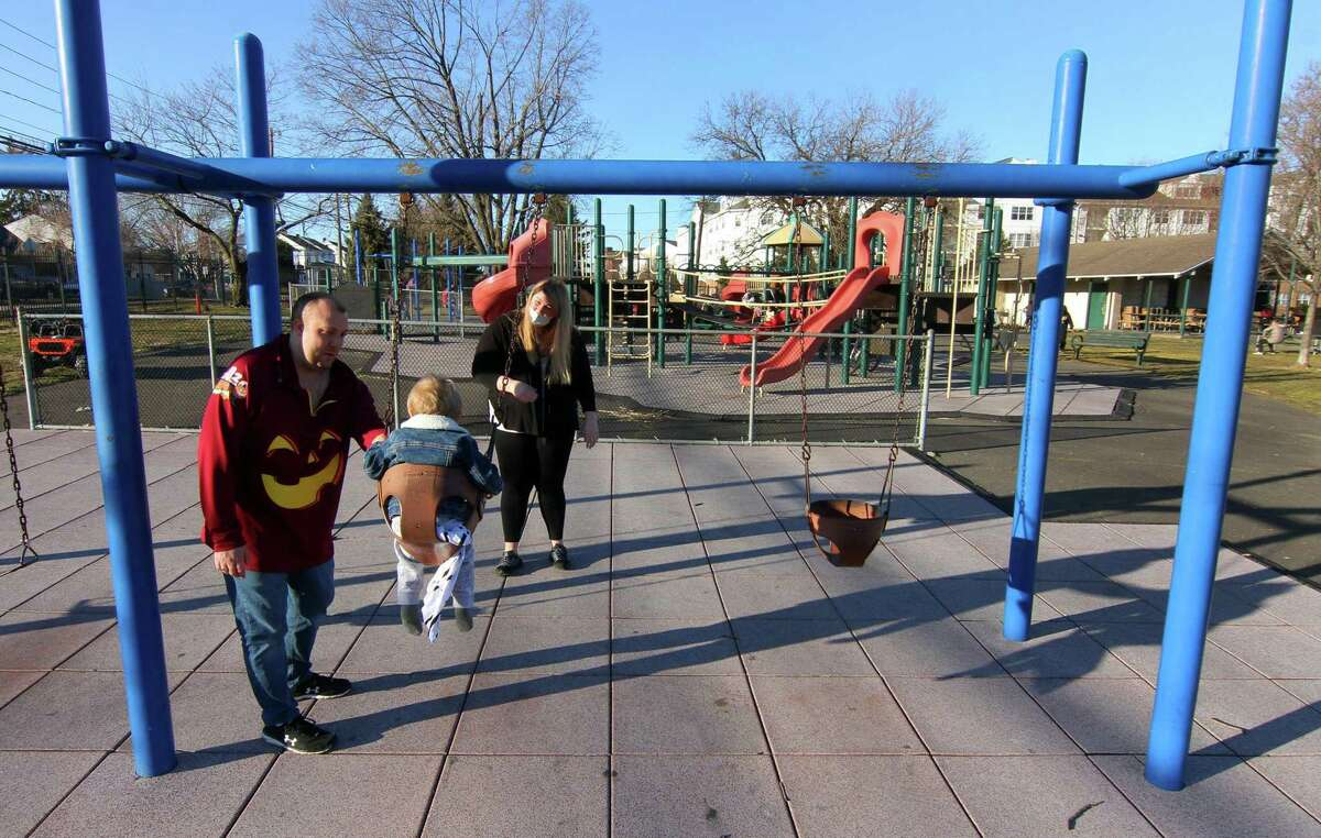 Mike and Chelsea Galgano push their son Luke, 1, on the swings at Bocuzzi Park in Stamford, Conn., on Friday Mar. 12, 2021. The Zoning Board approved the construction of a Harbor Education Center at the park, plus a bunch of improvements to the site in general.