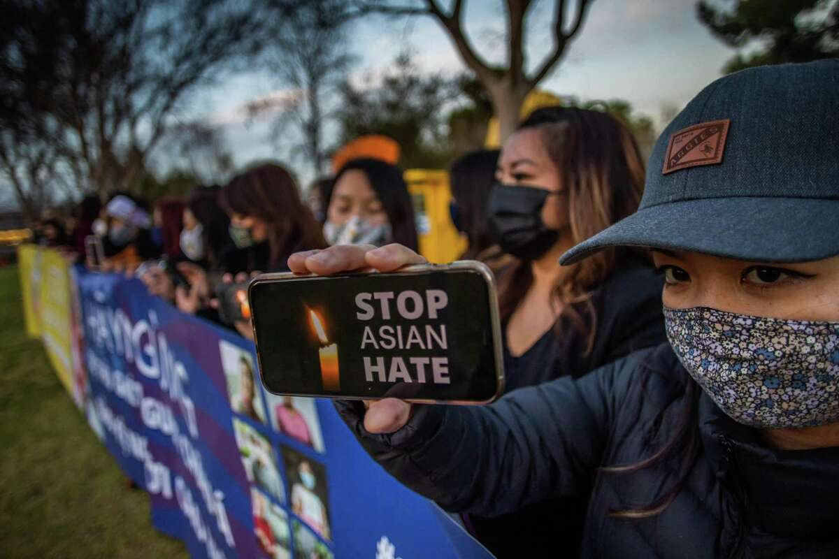 Julie Tran holds her phone during a candlelight vigil in Garden Grove, California, on March 17, 2021 to unite against the recent spate of violence targetting Asians and to express grief and outrage after yesterday's shooting that left eight people dead in Atlanta, Georgia, including at least six Asian women. - Police have said suspect Robert Aaron Long, a 21-year-old white man, has so far denied a racist motive for the three shootings in the southern US state of Georgia. (Photo by Apu GOMES / AFP) (Photo by APU GOMES/AFP via Getty Images)