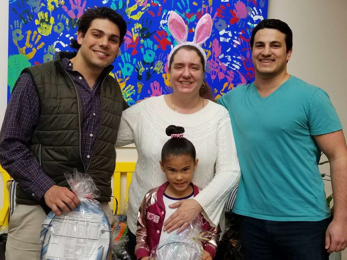DiMatteo Insurance in Shelton delivered 96 Easter baskets to four shelters in Norwalk and Stamford in 2019. Delivering Easter baskets and goodwill are third-generation family members Anthony DiMatteo of Bethany, left, along with his cousin, John Esposito of Middlebury, right. They are pictured with Tracy Bell, center, and Eliana Franchesi, 8, one of the happy gift basket recipients.