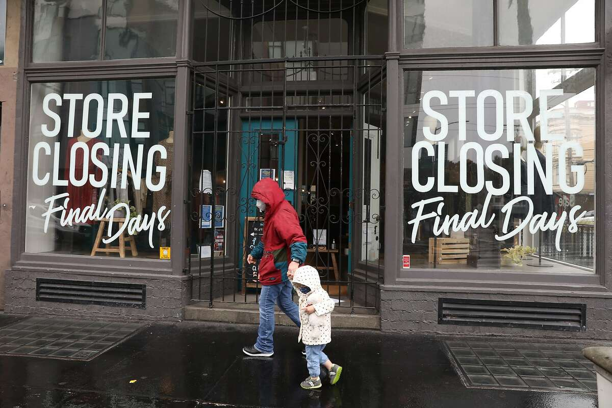 Maureen Verkamp holds the hand of grandaughter Isla Verkamp, 2, as they walk in the rain on Hayes Street past Acote in San Francisco. Acote, a French clothing boutique in Hayes Valley, closed permanently on March 21.