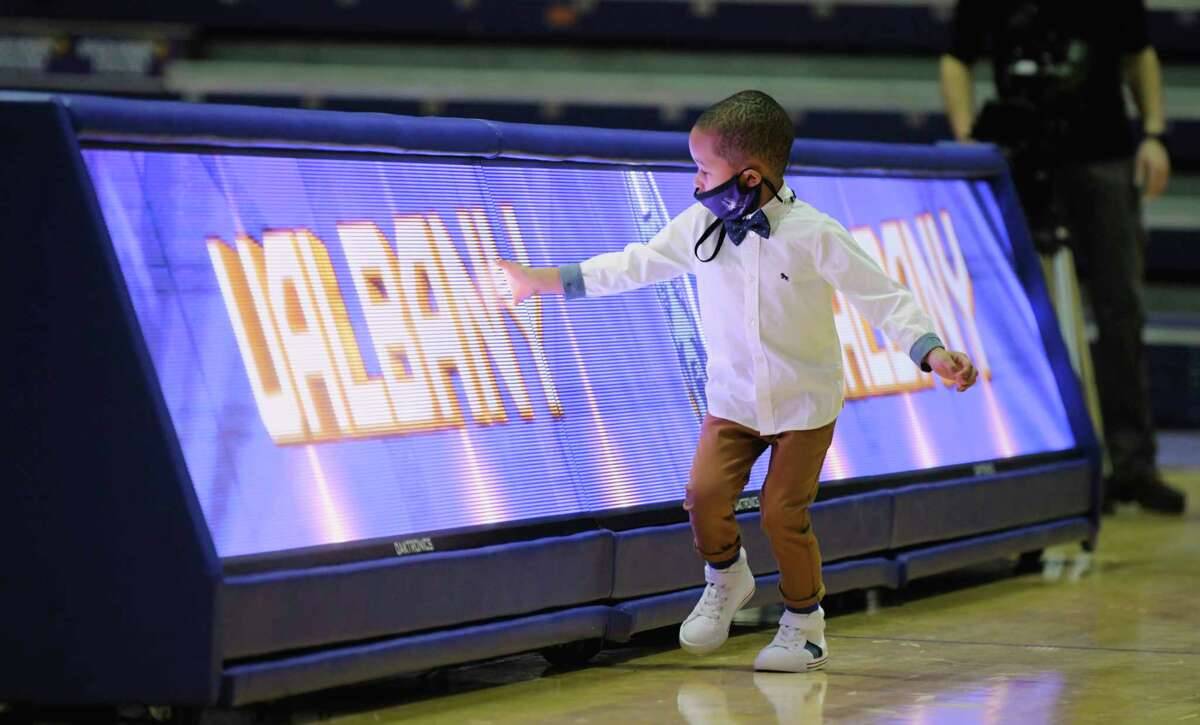 Tristan Killings, the son of new UAlbany men's basketball coach, Dwayne Killings, plays near an electronic banner following an event at the SEFCU Arena where Dwayne Killings was introduced as the new coach on Thursday, March 18, 2021, in Albany, N.Y. (Paul Buckowski/Times Union)