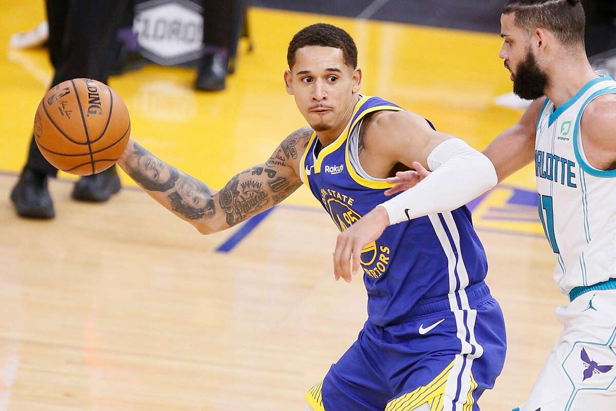 Golden State Warriors forward Juan Toscano-Anderson (95) looks to pass while defended by Charlotte Hornets forward Cody Martin (11) during an NBA game at Chase Center, Friday, Feb. 26, 2021, in San Francisco, Calif.
