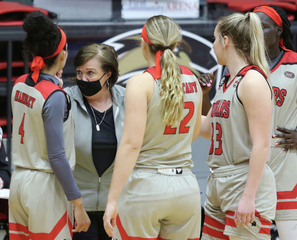 SIUE coach Paula Buscher (second left) talks with her Cougars during a timeout in the second half of Thursday's OVC loss to Austin Peay at First Community Arena in Edwardsville.