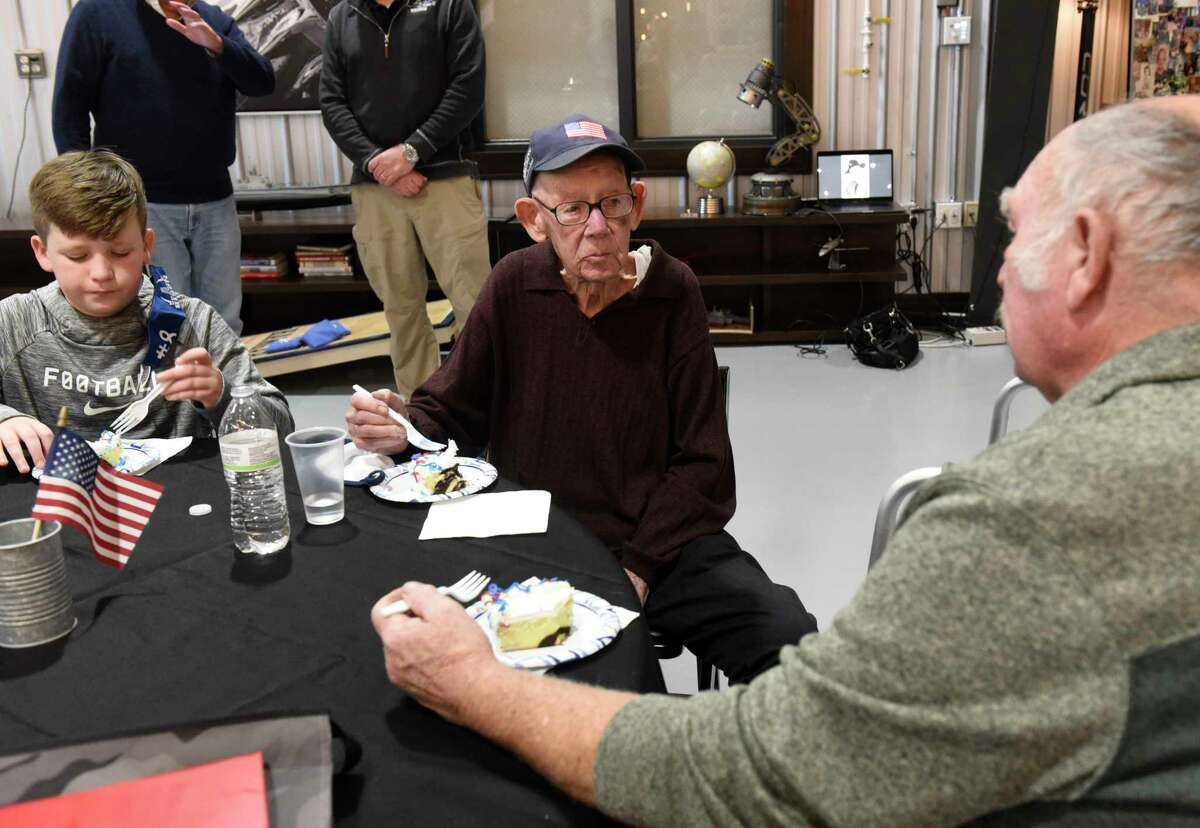 Captain Edmund Steffler, center, enjoys a piece of cake as he celebrates his 100th birthday with friends and family at The Hangar 743 on Thursday, March 18, 2021 in Latham, N.Y. The local WWII Veteran served bravely for the United States, in Hawaii, and the Island of Tinian in a B-29 Superfortress very heavy bombardment squadron with the Army Air Corps. (Lori Van Buren/Times Union)