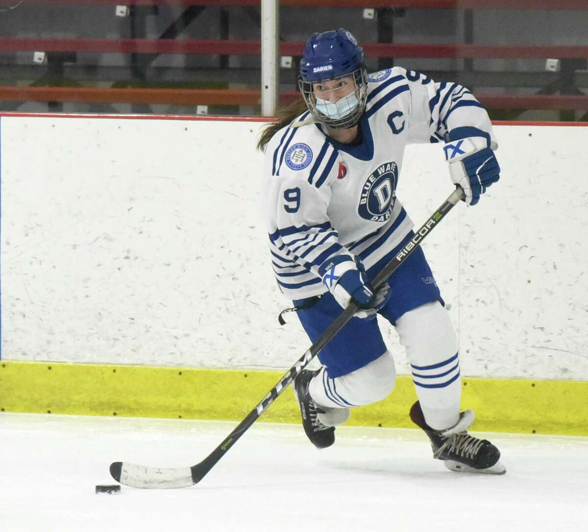 Darien senior Kate Bellissimo controls the puck against New Canaan at the Darien Ice House on March 6.