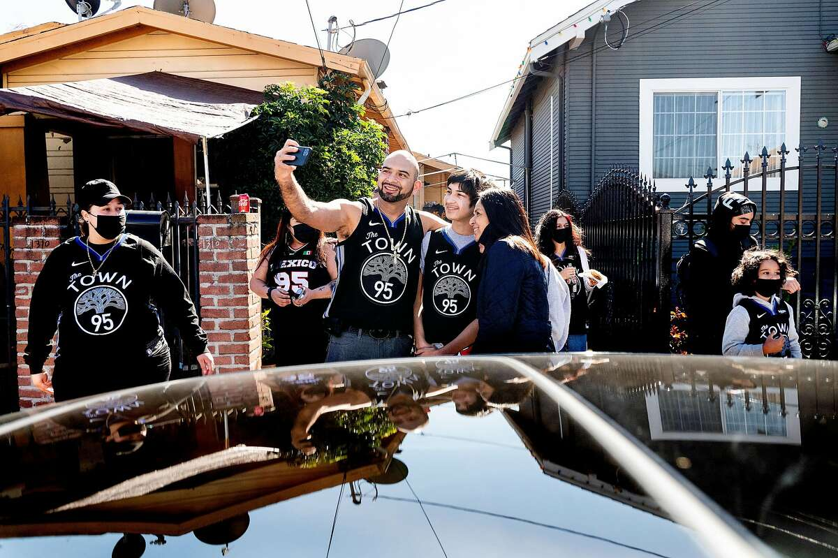 Golden State Warriors forward Juan Toscano-Anderson's uncle Macario Toscano, Jr. takes a photo with family members outside Toscano-Anderson's childhood home in Oakland, Calif., on Sunday, Feb. 28, 2021. From left to right are Macario Toscano, Jr., Ryan Toscano and Sandra Toscano.