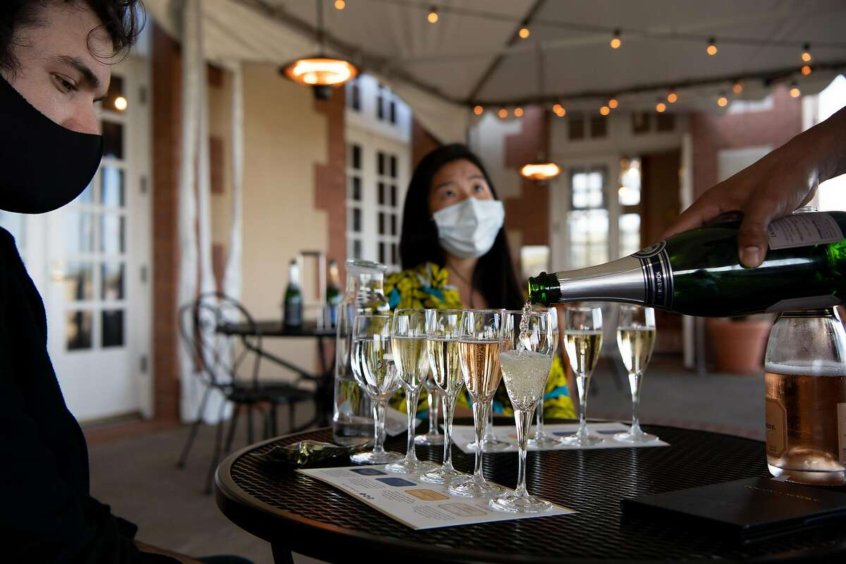 Edith Chao, right, and Aaron Lewis enjoy a wine tasting at Domaine Carneros in Napa. Wineries will be able to open tasting rooms as counties move into the orange tier with COVID criteria improving.