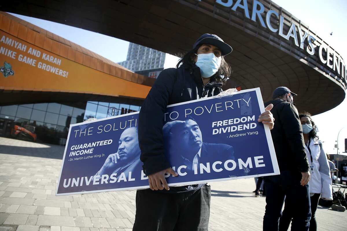 A man holds a campaign sign as New York City mayoral candidate Andrew Yang campaigns at Barclays Center on March 03, 2021 in the Brooklyn borough of New York City. Yang made Universal Basic Income a hallmark of both his 2020 presidential and current mayoral campaigns, and as the pandemic continues, the concept is making a resurgence in communities across the nation like Ulster County.