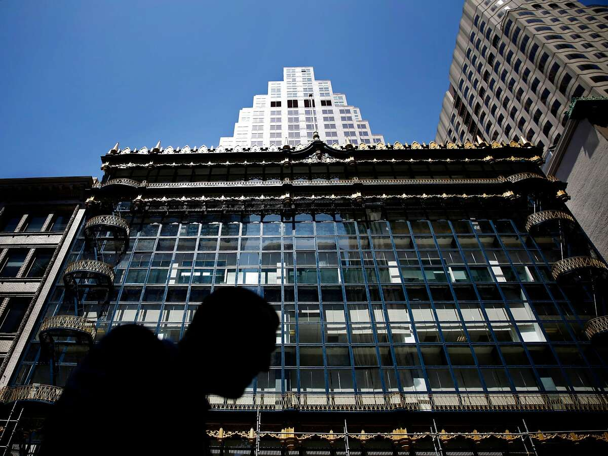 A pedestrian passes in front of Willis Polk's Hallidie Building in San Francisco on April 26, 2013.