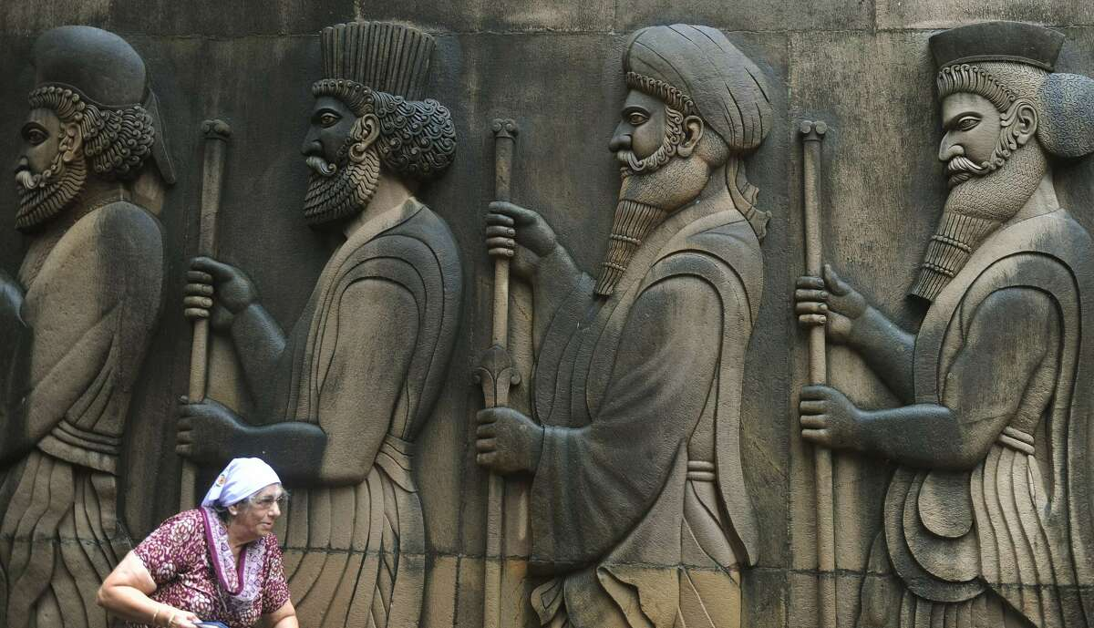 In this 2010 photo, an Indian Parsi woman walks by relief figures of knights at a fire temple after offering prayers on the Parsi New Year or Nowruz in Mumbai, a spiritual home to Zoroastrianism The Zoroastrian community worldwide is tiny compared to Islam or Hinduism. But its members have been hugely successful at forging communities that adapt to new homelands. It's one of the world's oldest religions, many of whom descend from Persians who fled to India to escape persecution more than 1,000 years ago.
