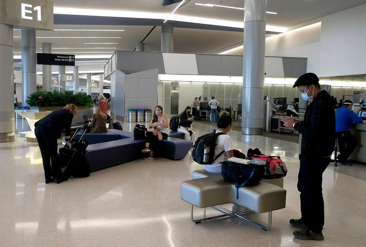 Travelers organize carry-on items after security screening at San Francisco International Airport in October.