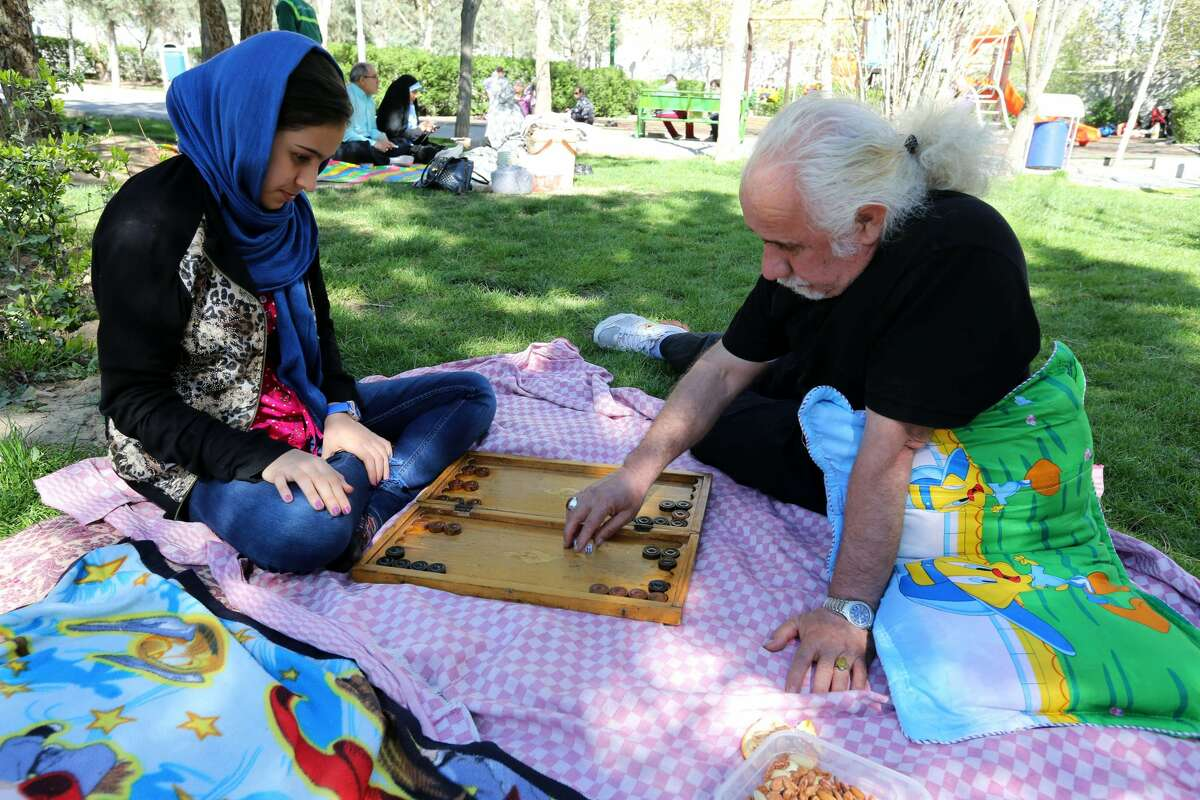 Iranians play backgammon at a park in northern Tehran in 2015 as they celebrate Nowruz which people spend outdoors to picnic with family and friends. Nowruz is the new year according to Zoroastrian tradition, still celebrated by Iranians even after Islam. The Zoroastrian holiday coincides with the first day of spring so picnic feasts are a common celebration.