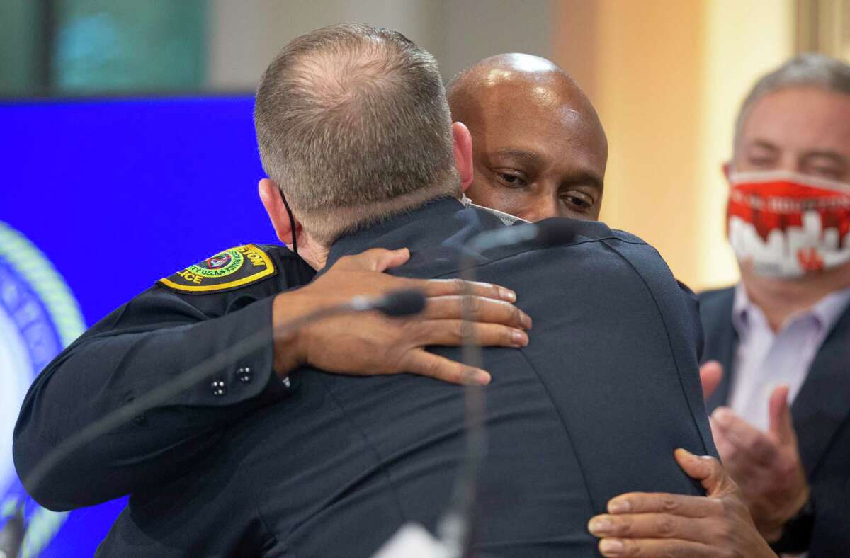 Houston Police Department Executive Assistant Chief Matt Slinkard hugs new HPD Chief Troy Finner, whom he has been working together as executive assistant chiefs in more than five years, during a press conference Thursday, March 18, 2021, at Houston City Hall in Houston. Houston Mayor Sylvester Turner announced that he has selected Finner to replace Chief Art Acevedo, who is leaving Houston to be the chief of Miami Police Department.
