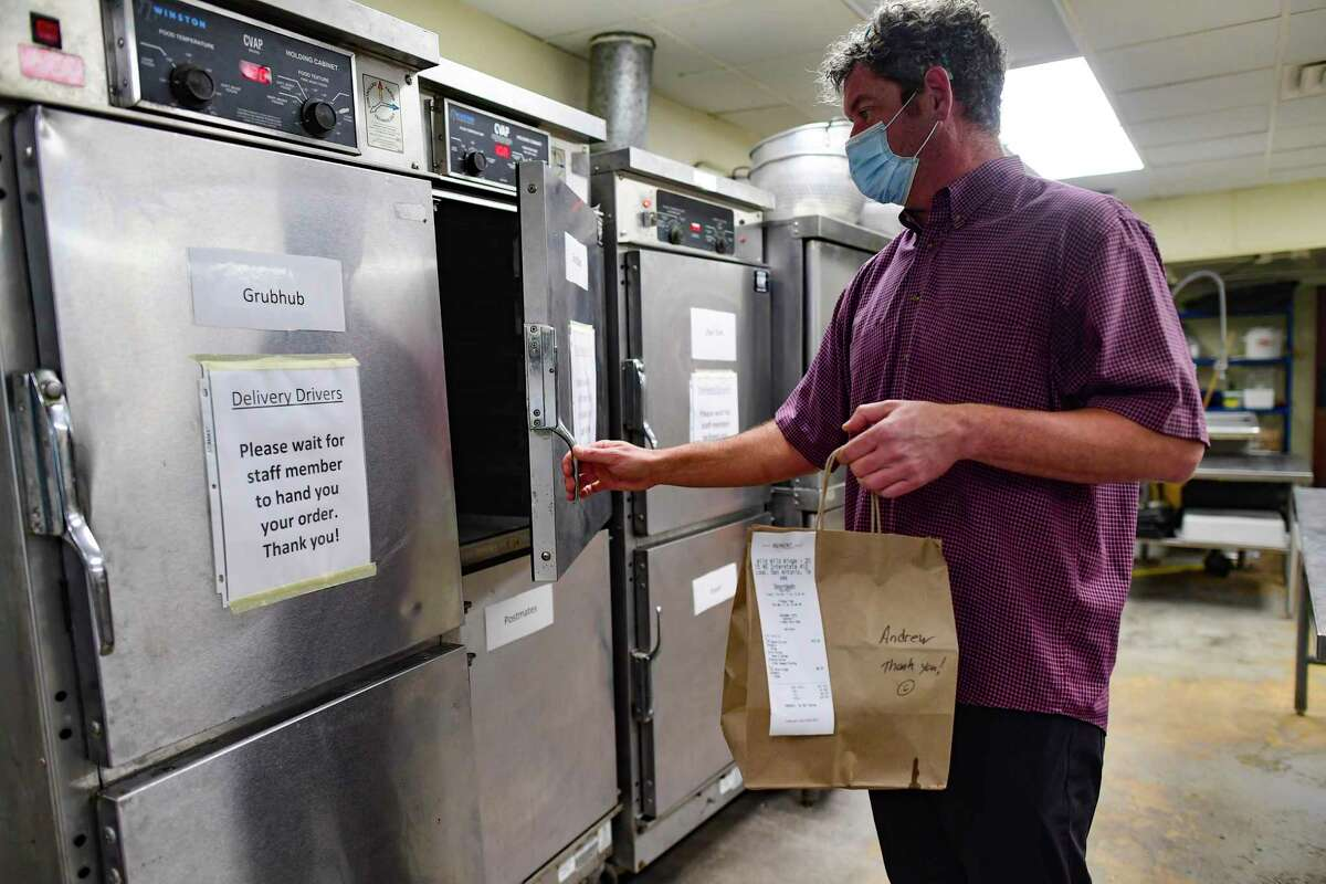 Chef Iverson Brownell puts a meal that is ready for pick up in a warmer at Ghost Kitchens SA.