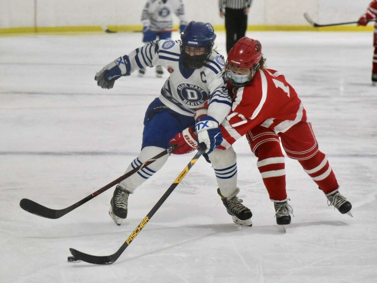 Darien's Nelle Kniffin, left, and Greenwich's Emiri Fukichi battle for the puck during the FCIAC girls ice hockey semifinals on Thursday at the Darien Ice House.
