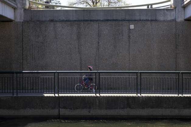 A children bikes through the underpass of Grogans Mill Road at Town Green Park along The Woodlands Waterway, Thursday, March 18, 2021, in The Woodlands. Temperatures through the weekend are expected to range between the 60s-70s according to the National Weather Service. Photo: Gustavo Huerta/Staff Photographer / Houston Chronicle © 2021