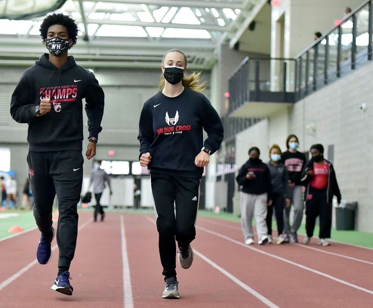 New Haven, Connecticut - Thursday - March 18, 2021: Wilbur Cross High School track team seniors Devin Cue who runs the 300-meter race, and Margo Pedersen and runs the in the 1000-meter at a dual meet Thursday at the Floyd Little Athletic Center in New Haven