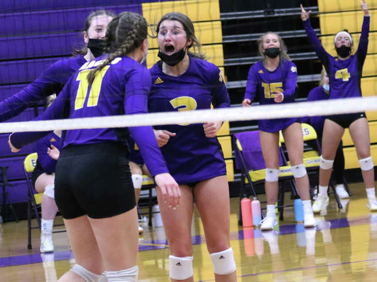 CM setter Maddie Brueckner (middle) celebrates with middle hitter Jackie Woelfel (11) after the connected on a set-kill against Jersey on Thursday night in Bethalto.