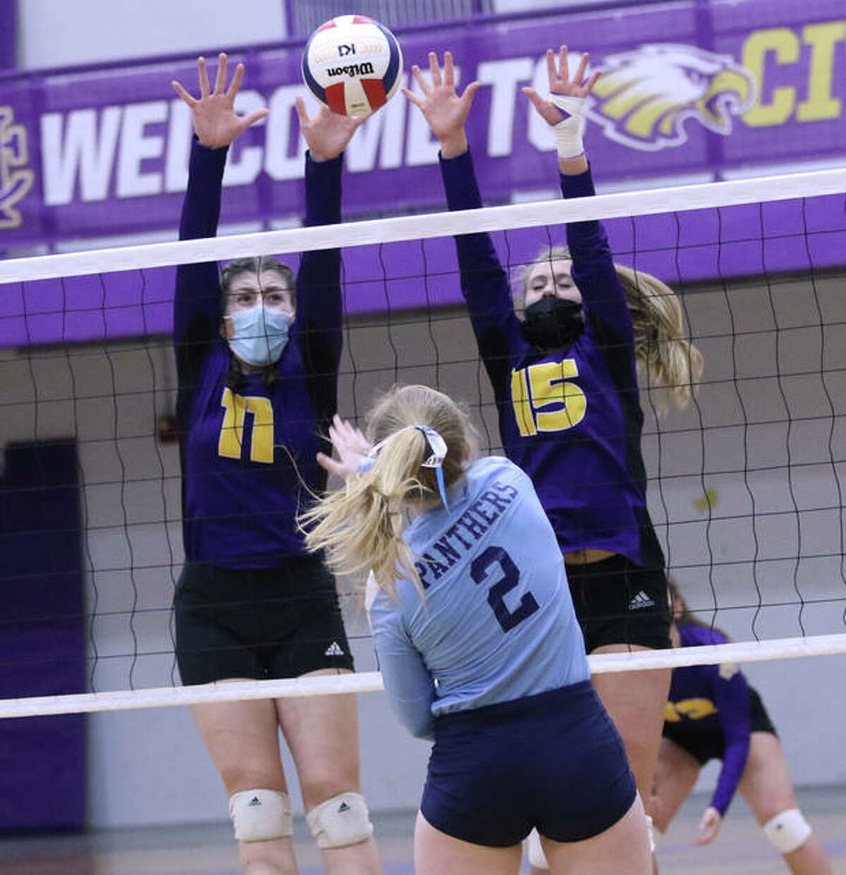 Jersey's Sally Hudson (2) deflects a shot off the top of a block put up by CM's Jackie Woelfel (11) and Annabelle Reno (15) on Thursday night in Bethalto.