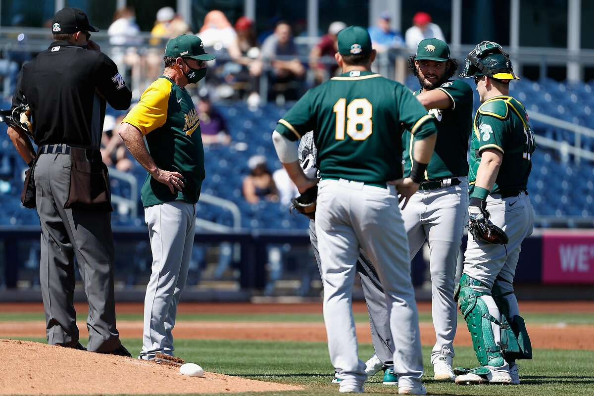 PEORIA, ARIZONA - MARCH 18: Starting pitcher Sean Manaea #55 of the Oakland Athletics talks with manager Bob Melvin, Mitch Moreland #18 and Sean Murphy #12 after being hit by a line-drive from the San Diego Padres during the first inning of the MLB spring training game at Peoria Sports Complex on March 18, 2021 in Peoria, Arizona. (Photo by Christian Petersen/Getty Images)