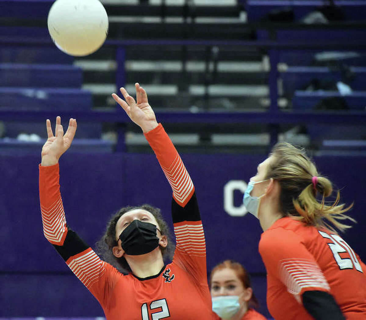 Edwardsville's Morgan Tulacro, left, sets a pass for teammate Storm Suhre on Thursday.