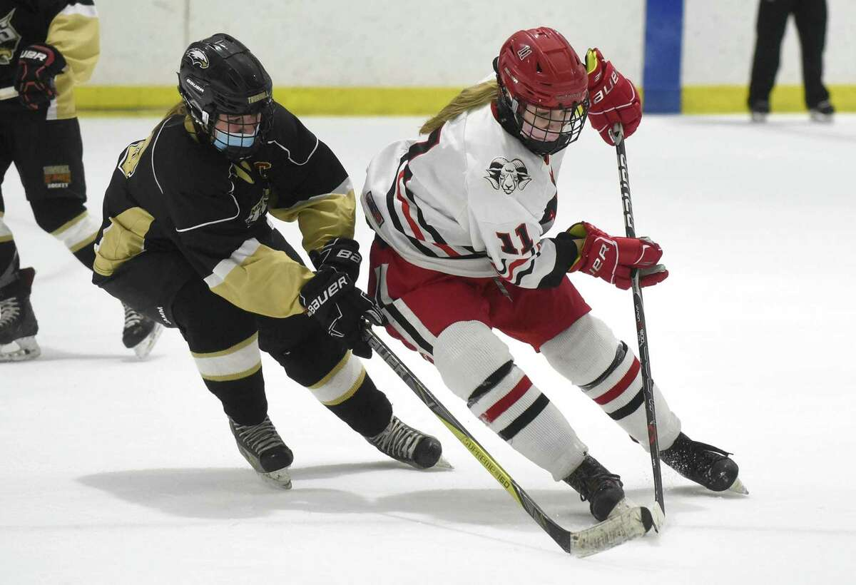 New Canaan's Kelly Benson (11) moves with the puck while Trumbull/St. Joseph's Megan McCarthy defends during the FCIAC girls ice hockey semifinals at the Darien Ice House on Thursday, March 18, 2021.