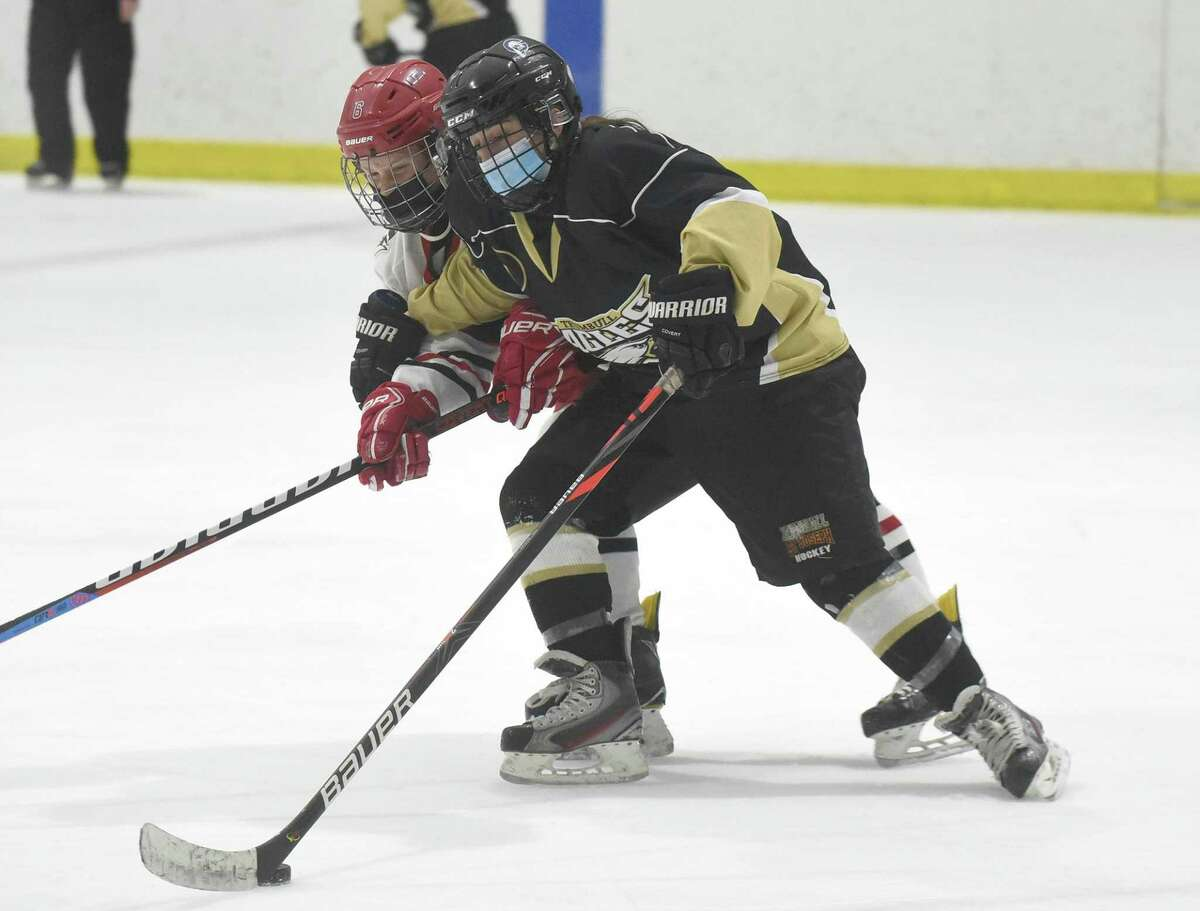 Megan McCarthy of the Trumbull/St. Joseph and Jade Lowe of New Canaan battle during the FCIAC girls ice hockey semifinals at the Darien Ice House on Thursday, March 18, 2021.