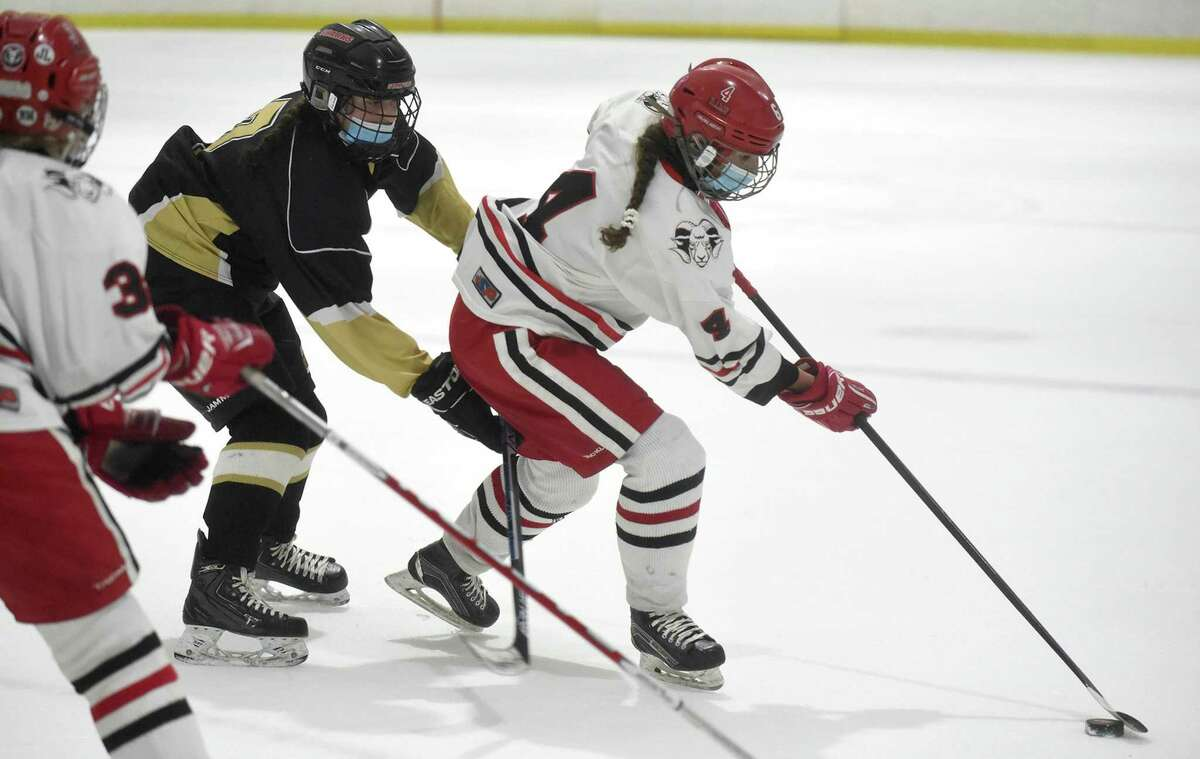 New Canaan's Kaleigh Harden (4) controls the puck against Trumbull/St. Joseph during the FCIAC girls ice hockey semifinals at the Darien Ice House on Thursday, March 18, 2021.