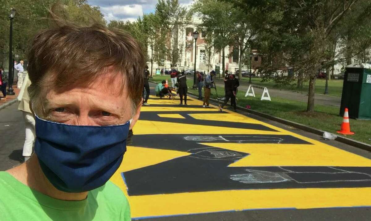 Mayor Justin Elicker takes a selfie in downtown New Haven in summer 2020 while joining community members in painting a Black Lives Matters mural.