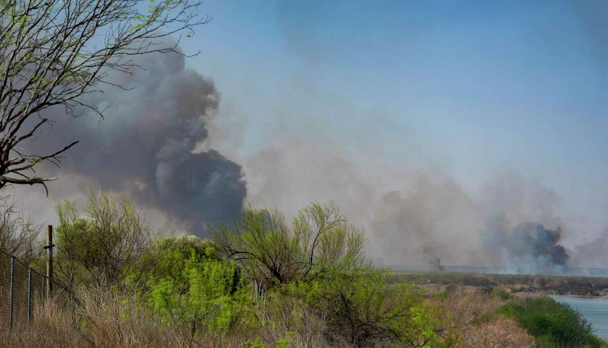 Smoke rises up from a private ranch near El Cenizo on Thursday March 18.  Fires near the Rio Grande are shown below on Wednesday night.