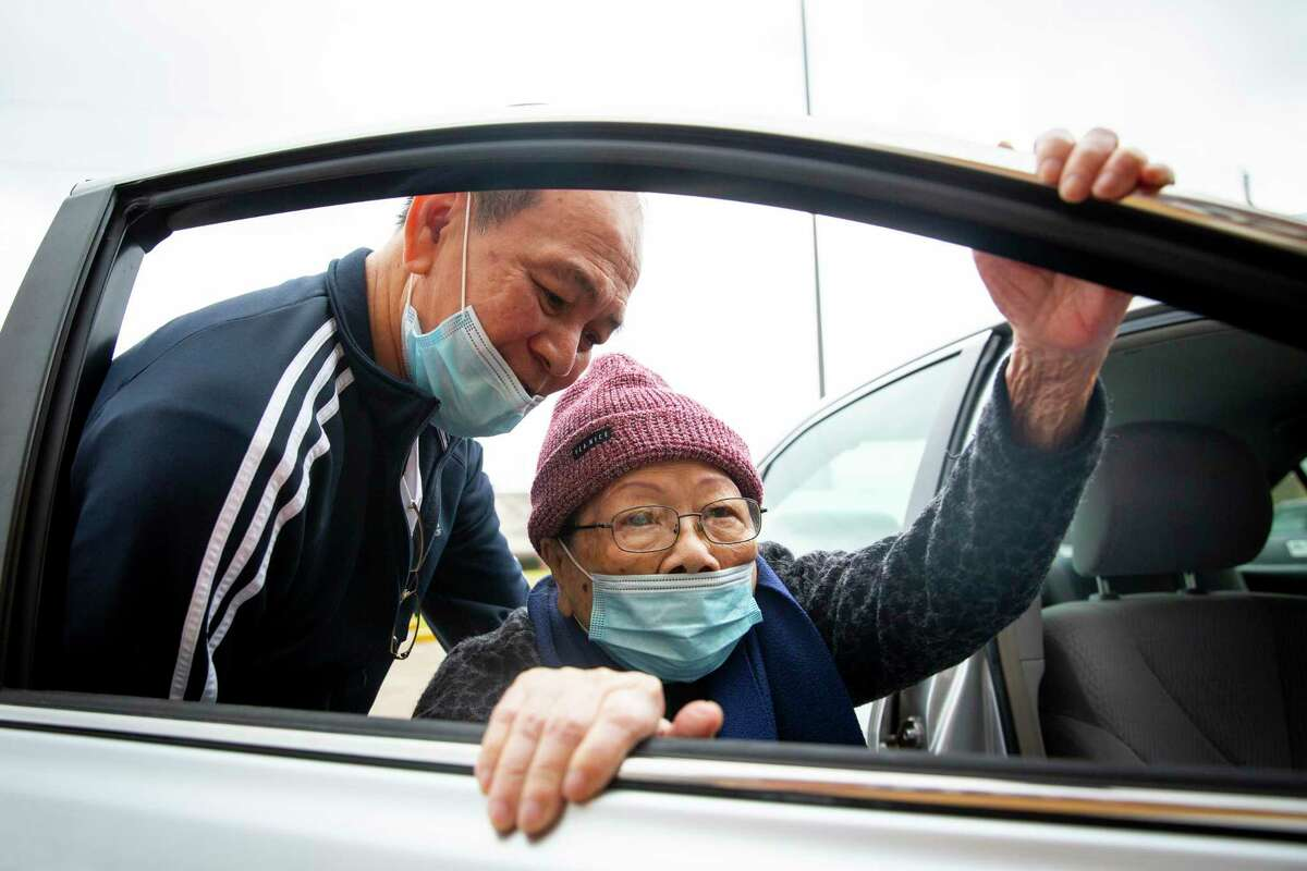Hiep Pham helps his mother, Hao Nguyen, back into their vehicle after receiving a COVID-19 vaccine at HOPE Clinic.