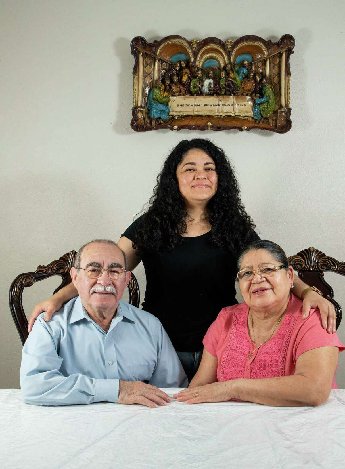 Edith Sorto, center, and her parents Santos, left, and Hilda Molina pose for a portrait in their dinning room Wednesday, March 17, 2021, in Houston. Sorto, 40, handles her parents' doctor's appointment, medications and making sure they were able to find a COVID-19 vaccine. Her parents don't speak English, don't have much technological knowledge and don't drive. Edith has had to figure everything out, mostly on her own, on her parents' behalf.